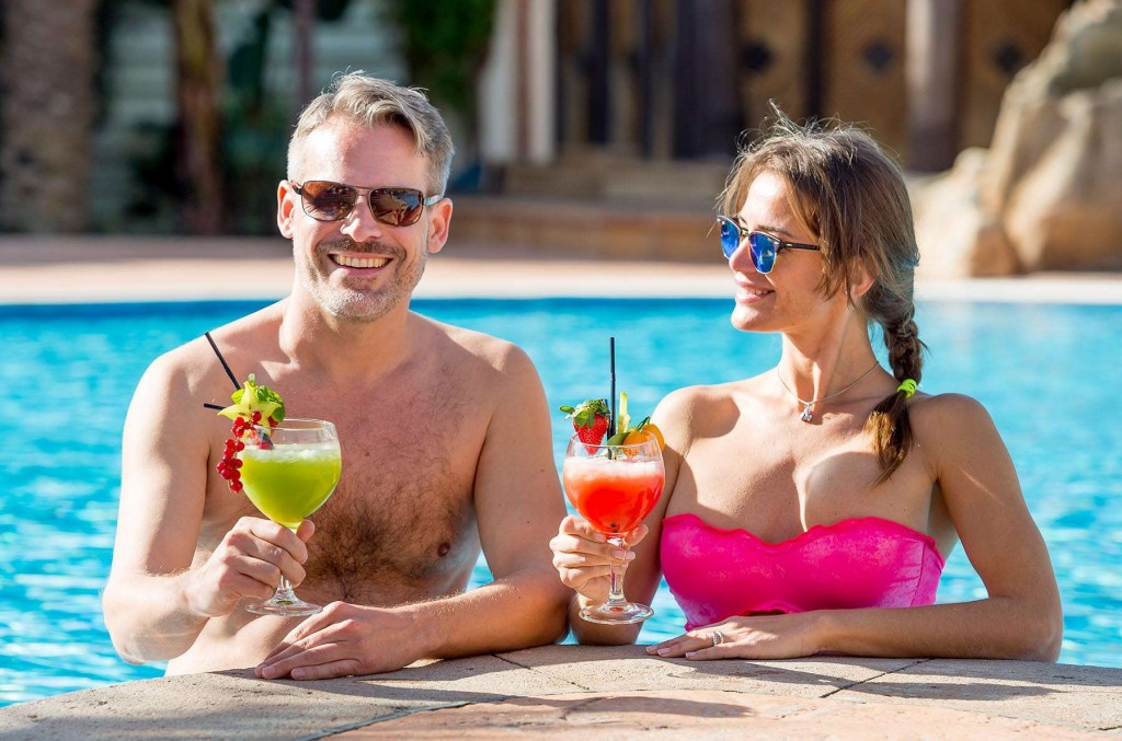 Guests enjoying the sun in the pool with refreshments